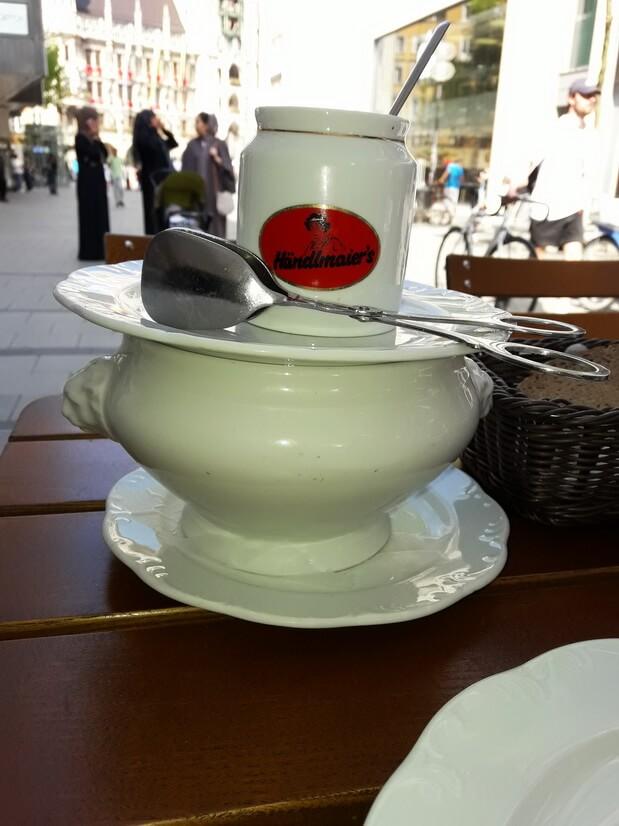 Мюнхенские белые сосиски Вайсвурст подаются в глубокой тарелке и со сладкой горчицей.